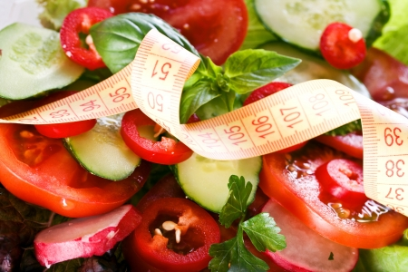 Vegetables and centimeter. Centimeter on the background of salad photo