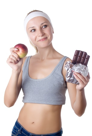 Young woman having a dilemma between fruit and chocolate - isolated over white