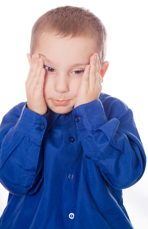 portrait of sad crying little boy covers his face with hands photo