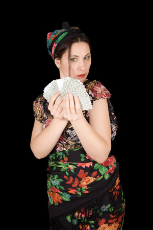 Gypsy woman with cards in hand on black background photo