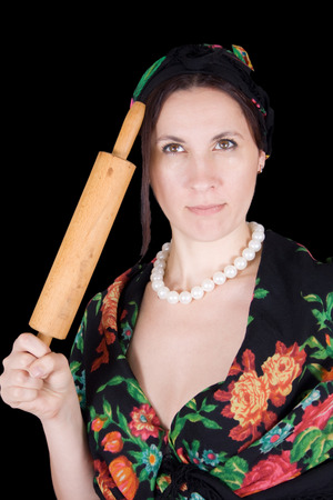 woman in a bandanna with a rolling pin in her hand on a black background photo