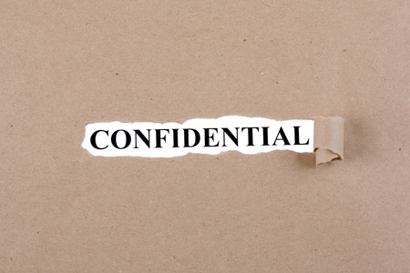 confidentiality: Word confidencial appears under the torn brown paper