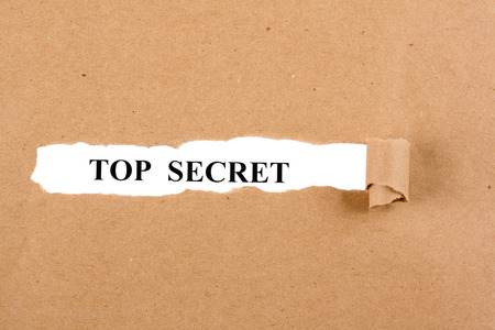Word top secret appears under the torn brown paper Stock Photo