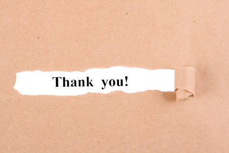 appears: Word thank you appears under the torn brown paper Stock Photo