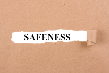 safeness: Word safeness appearing behind torn brown paper.