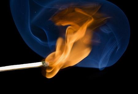 Brandende lucifer en blauwe rook op een zwarte achtergrond