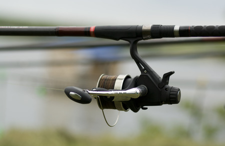 sportfishing: Fishing reel near the shore waiting for a big fish.