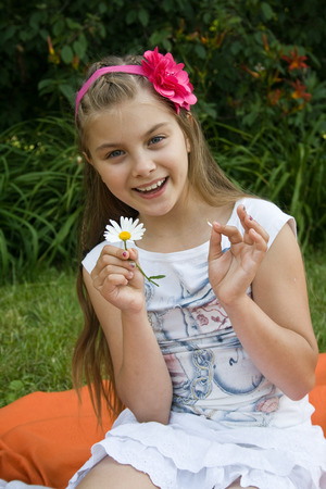 Girl guesses, tearing off petals on camomile, against green summer garden.