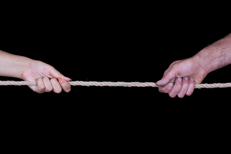 dissension: Female and male hands pulling rope Stock Photo
