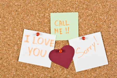 I Love You, call me and sorry note pinned to a cork memory bulletin board. photo