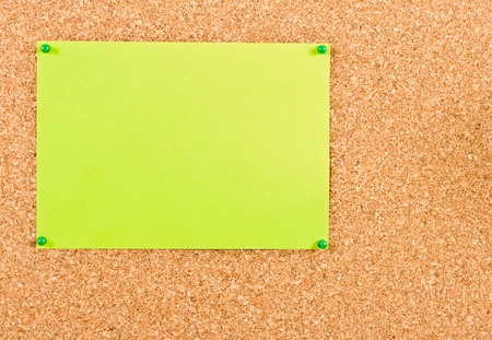 attach: Green sheet of paper attached to corkboard buttons Stock Photo