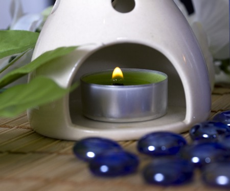 lit candle in aromatherapy lamp on a background of green leaves Stock Photo