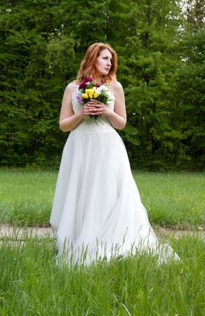 eyes hazel: Portrait of a beautiful and happy bride with a bouquet on a background of green forest