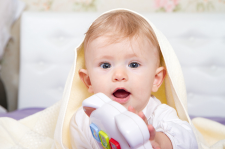 poking: Smiling baby boy under blanket.