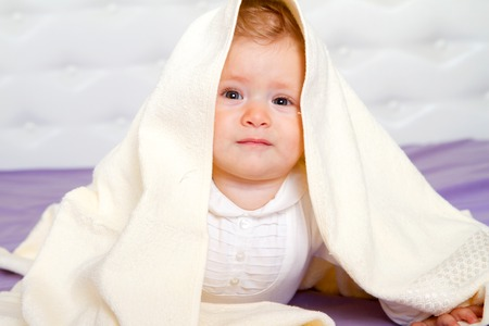 Smiling baby boy under blanket.