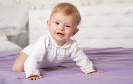 Neonato sorridente sotto la coperta.
