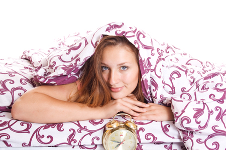 sleek: Sleek and happy young woman lies under a blanket with an alarm clock