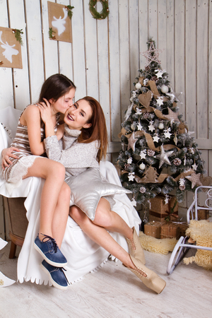 Daughter hugging and kissing her mother near the Christmas tree. Stock Photo