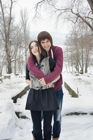 Happy loving couple on walk in winter park