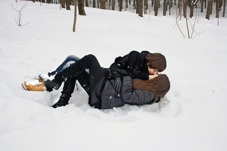 Man and woman in captivity of love, kissing lying on the snow