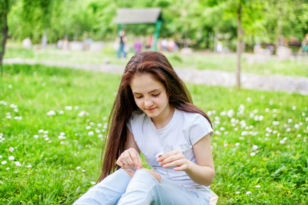 Young woman sits on the grass and guesses on a daisy