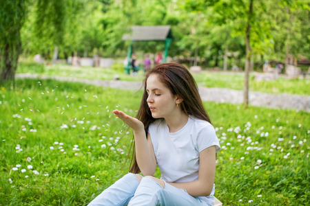 Girl sits in the park on the grass and blows off the flower petals from her palm Stock Photo