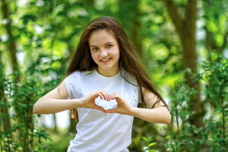 Attractive woman makes heart shape with her hands in the forest. Hiking theme