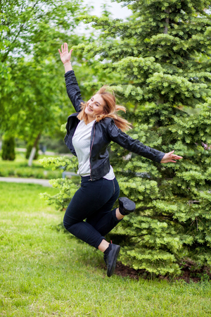 Woman jumping on path from the back.