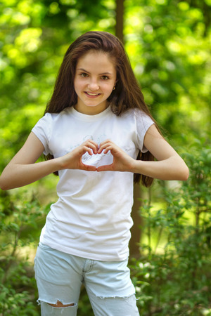 Young girl shows her hands a heart in the park Stock Photo