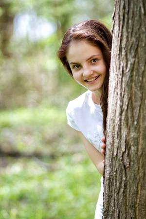 A girl smiles as she peeks out from behind a tree. Stock Photo