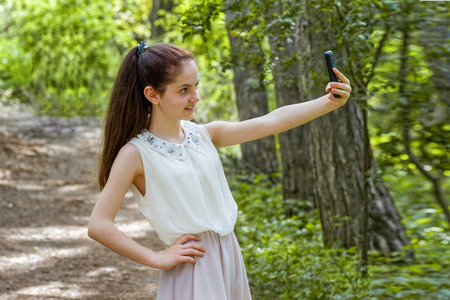 Girl in the park takes pictures of herself on the phone