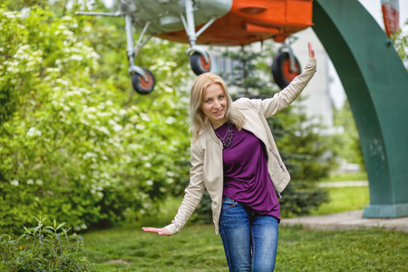 Rejoicing happy woman in flying motion smiling full of joy and vitality in summer or spring forest.