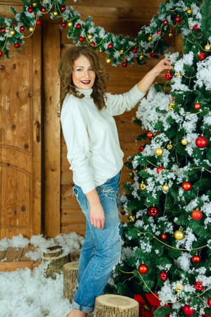 Beautiful woman in new year interior dresses up Christmas tree. photo