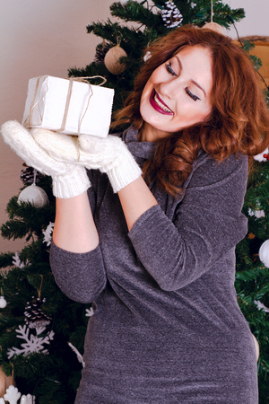 Beautiful woman enjoys gift to have dressed up Christmas tree photo
