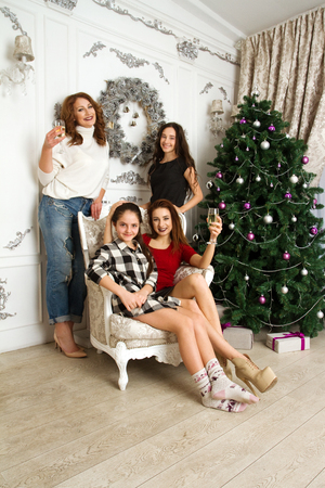 The friendly family at the Christmas tree with a glass of champagne photo