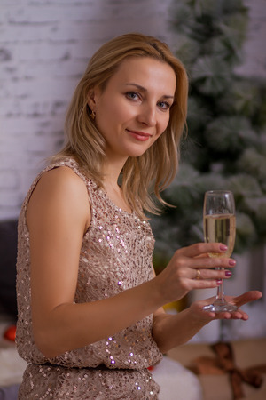 Portrait of blond woman with glass of champagne on Christmas