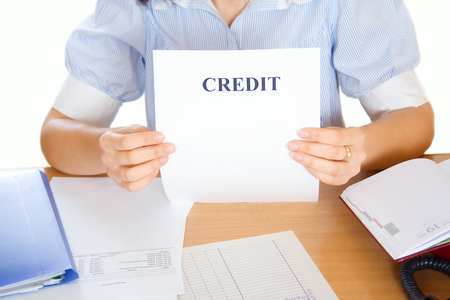 Woman holds a sheet of paper on which a credit is written