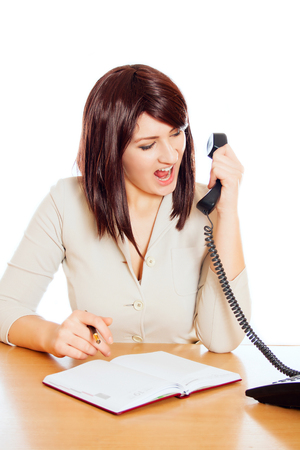 Businesswoman sitting at her desk and screaming into a phone