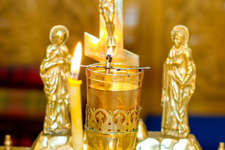 Close up golden and red censer hanging in church