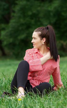 Beautiful girl sits on lawn. Stock Photo