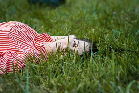 Beautiful girl lies on lawn. Stock Photo