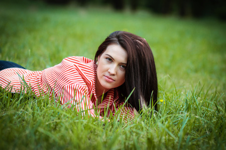Young attractive girl lies on a green lawn in the city park. Happy youth.