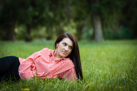 Beautiful young woman lies down on the grass smiling Stock Photo