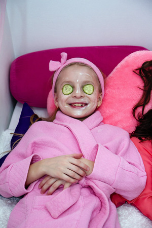 Cosmetic procedures for girls. A girl with cucumbers in her eyes and a mask is lying on the bed Stock Photo