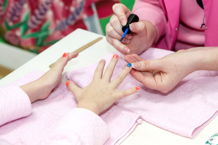 Close up of pretty young women painting nails with her girlfriend