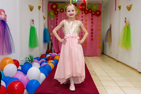 Happy beautiful little girl shows dress and having fun
