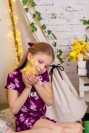 Portrait of cute little girl with duckling in easter decorations Stock Photo