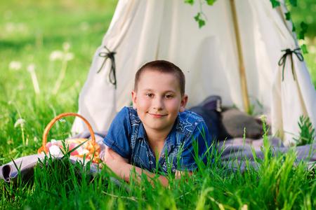 Joyful boy lies on the green grass