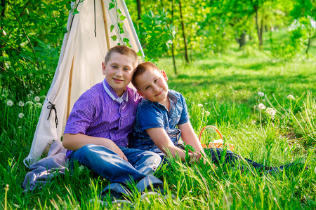 Portrait of brothers sitting together on grass in a park Stock Photo