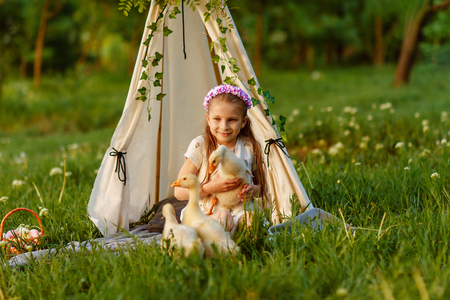 Little joyful girl sitting on grass with goose